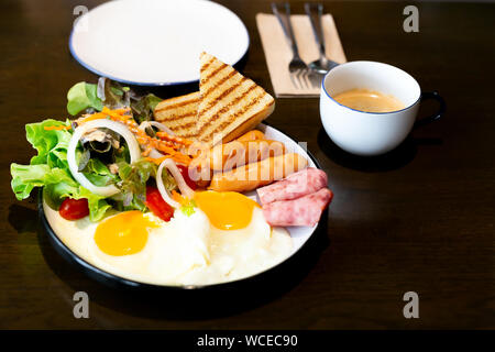 Breakfast set, with vegetable, ham, bacon, fried egg, sausage and cup of coffee. - Stock Photo