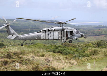 U.S. Marines with 3rd Reconnaissance Battalion, 3rd Marine Division, and Sailors with Explosive Ordinance Disposal Mobile Unit 5, execute a fast rope insert from a MH-60S Seahawk helicopter during exercise HYDRACRAB in Santa Rita, Guam, Aug. 20, 2019. HYDRACRAB is a multilateral exercise conducted by U.S. Marines and Sailors with military service members from Australia, Canada, and New Zealand. The purpose of this exercise is to prepare the participating Explosive Ordnance Disposal forces to operate as an integrated, capable, and effective allied force ready to operate in a changing and comple - Stock Photo