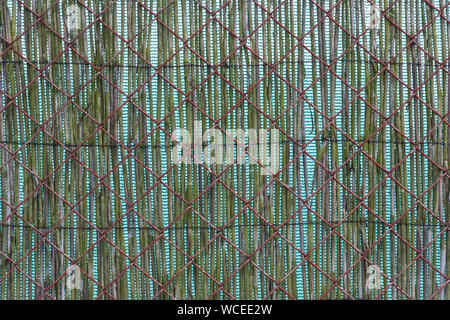 Texture of double fence. Rusty metallic mesh and opaque reed mat. Detail of garden fencing from old brown wire netting. Green matting  in background. - Stock Photo