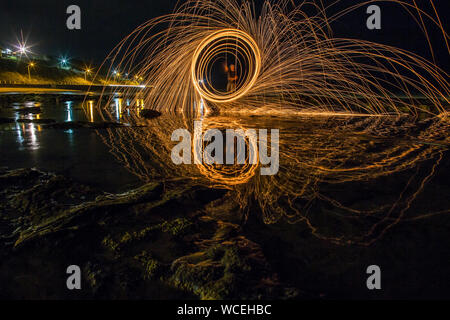 Man With Wire Wool Standing On Shore At Beach - Stock Photo