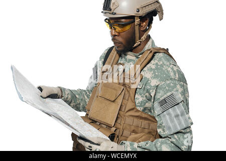 American soldier wearing uniform and helmet holding map and looking at locality objects. African male soldier in armour navigating with map. Concept of army. - Stock Photo
