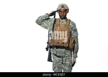 Front view of African male soldier serve in army, hears and executes orders. American soldier wearing uniform with modern weapon machine holding hand near head. White studio background. - Stock Photo