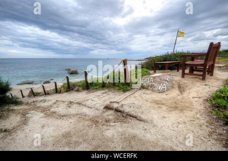 Empty Chairs On Footpath By Sea Against Cloudy Sky