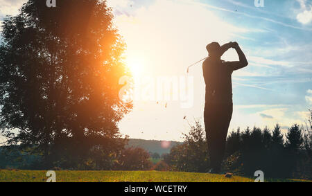 Silhouette Man Playing Golf Against Sky During Sunset - Stock Photo