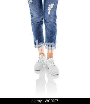 Legs in jeans and white sneakers isolated on a white background. - Stock Photo