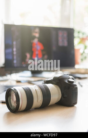 Professional dslr photocamera with long white zoom lens on desk in photo studio.Freelance photographer camera and computer screen with retouched image - Stock Photo