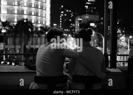 Rear View Of Couple Kissing In City At Night - Stock Photo