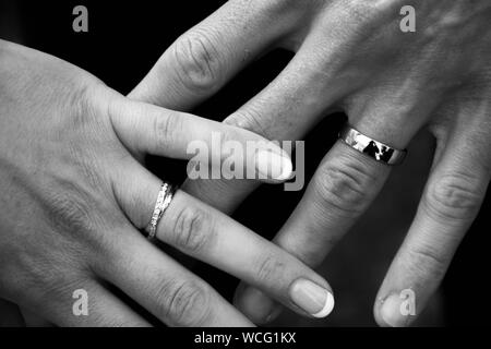 Cropped Hands Of Bride And Groom Showing Wedding Rings - Stock Photo