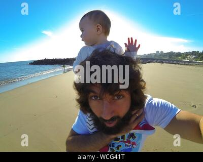 Portrait Of Father Carrying Daughter On Shoulder At Beach Against Sky - Stock Photo