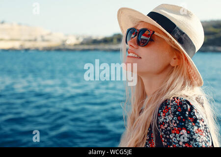 Happy blonde Mediterranean woman in hat amazed by panorama on cruise ship Stock Photo