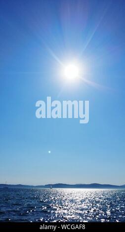 Sun Shining Over Sea Against Clear Blue Sky - Stock Photo