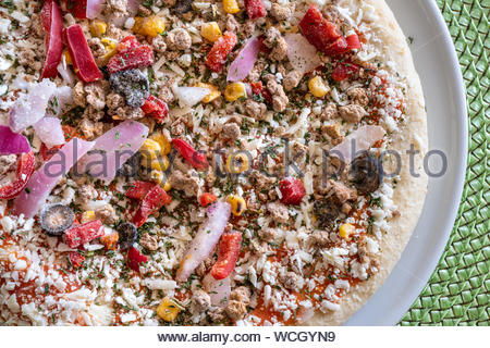 Frozen raw Southwestern pizza. The traditional dish of the Italian cuisine has onions, red peppers, black olives, corn, and mozzarella cheese. - Stock Photo