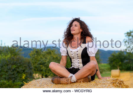 Woman Looking Away While Sitting On Hay Bale Against Sky - Stock Photo