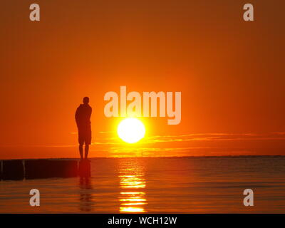 Silhouette Man Standing On Pier Over Sea Against Orange Sky - Stock Photo