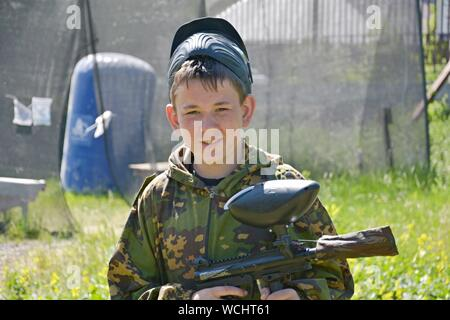 Portrait Of Boy Wearing Camouflage Clothing On Field - Stock Photo