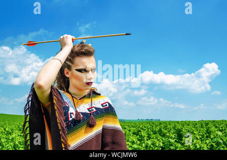 Amazon girl aggressive makeup, in a poncho, cosplay in the field, holds a bow and arrow. Paganism, feminism, independence, tribe