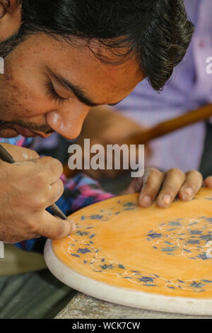 Craftsman employing traditional techniques and shaping pieces of marble and semi-precious stones on a hand-powered emery wheel, Taj Mahal, Agra, India - Stock Photo
