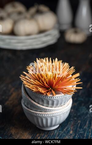 Orange Chrysanthemum Flower In Stack Of Bowls On Table - Stock Photo