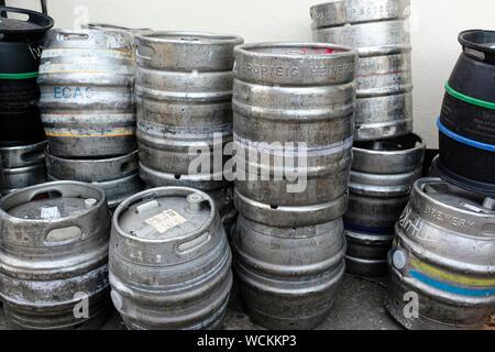 Stainless steel beer barrels, kegs, casks outside a pub - Stock Photo