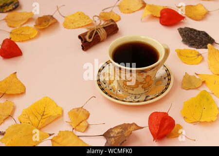Autumn composition with cup of coffee and cinnamon sticks frame made of autumn leaves, horizontal orientation, copy space - Stock Photo