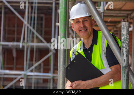 Male builder foreman, construction worker, surveyor or site manager holding a clipboard, wearing a white hard hat and hi vis vest and smiling - Stock Photo