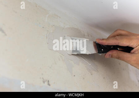 The worker covers the uneven walls, man's hands with a spatula and putty, apartment repair - Stock Photo