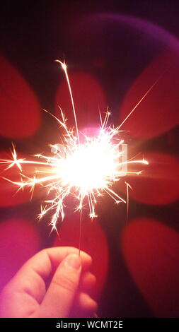 Close-up Of Hand Holding Sparklers - Stock Photo