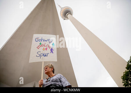 Berlin, Germany. 28th Aug, 2019. 'The sidewalk is my lane' is a pedestrian demonstration against parked cars, cyclists and e-scooters on sidewalks on the poster of a participant sitting at the foot of the Berlin TV tower. Some demonstrators carry swimming noodles as symbolic spacers. The German Foot Traffic Association (FUSS) has called for the demonstration. Credit: Christoph Soeder/dpa/Alamy Live News - Stock Photo