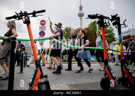 Berlin, Germany. 28th Aug, 2019. Participants of a pedestrian demonstration against parking cars, cyclists and e-scooters on sidewalks walk past parking e-scooters with swimming noodles. Some demonstrators carry swimming noodles as symbolic spacers. The German Foot Traffic Association (FUSS) has called for the demonstration. Credit: Christoph Soeder/dpa/Alamy Live News - Stock Photo