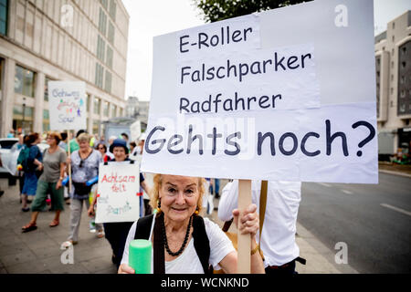 Berlin, Germany. 28th Aug, 2019. 'E-scooter, parking wrong, cyclist, is it still possible?' is written on the poster of a participant at a pedestrian demonstration against parked cars, cyclists and e-scooters on sidewalks. Some demonstrators carry swimming noodles as symbolic spacers. The German Foot Traffic Association (FUSS) has called for the demonstration. Credit: Christoph Soeder/dpa/Alamy Live News - Stock Photo