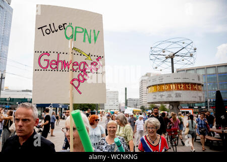 Berlin, Germany. 28th Aug, 2019. The train of a pedestrian demonstration against parked cars, cyclists and e-scooters on sidewalks passes the world time clock on Alexanderplatz. Some demonstrators carry swimming noodles as symbolic spacers. The German Foot Traffic Association (FUSS) has called for the demonstration. Credit: Christoph Soeder/dpa/Alamy Live News - Stock Photo