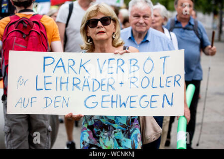 Berlin, Germany. 28th Aug, 2019. 'Parking prohibition for rental bikes and scooters on the sidewalks' is written on the poster of a participant at a pedestrian demonstration against parked cars, cyclists and e-scooters on the sidewalks. Some demonstrators carry swimming noodles as symbolic spacers. The German Foot Traffic Association (FUSS) has called for the demonstration. Credit: Christoph Soeder/dpa/Alamy Live News - Stock Photo