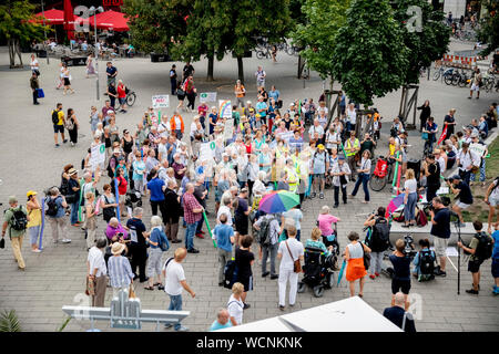 Berlin, Germany. 28th Aug, 2019. Participants of a pedestrian demonstration against parked cars, cyclists and e-scooters on sidewalks gathered at the foot of the Berlin TV tower for the closing rally. Some demonstrators carry swimming noodles as symbolic spacers. The German Foot Traffic Association (FUSS) has called for the demonstration. Credit: Christoph Soeder/dpa/Alamy Live News - Stock Photo