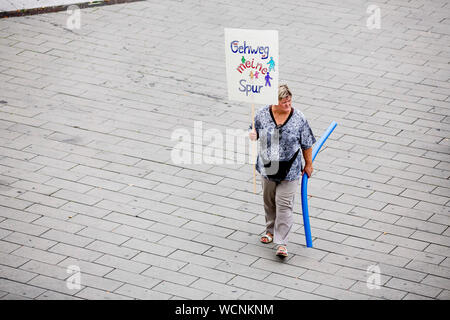 Berlin, Germany. 28th Aug, 2019. 'The sidewalk is my lane' is written on a participant's poster during a pedestrian demonstration against parked cars, cyclists and e-scooters on sidewalks. Some demonstrators carry swimming noodles as symbolic spacers. The German Foot Traffic Association (FUSS) has called for the demonstration. Credit: Christoph Soeder/dpa/Alamy Live News - Stock Photo