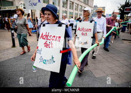 Berlin, Germany. 28th Aug, 2019. Participants of a pedestrian demonstration against parked cars, cyclists and e-scooters on sidewalks hold swimming noodles as symbolic spacers. The German Foot Traffic Association (FUSS) has called for the demonstration. Credit: Christoph Soeder/dpa/Alamy Live News - Stock Photo