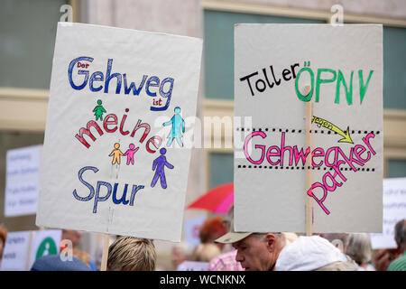 Berlin, Germany. 28th Aug, 2019. Two posters can be seen at a pedestrian demonstration against parked cars, cyclists and e-scooters on sidewalks. Some demonstrators carry swimming noodles as symbolic spacers. The German Foot Traffic Association (FUSS) has called for the demonstration. Credit: Christoph Soeder/dpa/Alamy Live News - Stock Photo