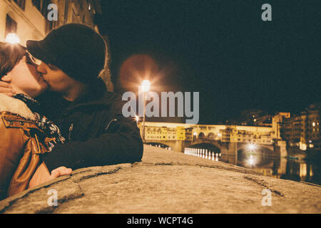 Young Couple Kissing By Bridge In City At Night - Stock Photo