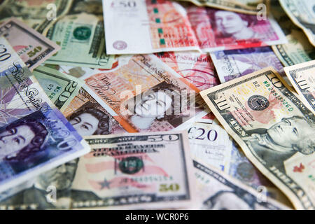 August 28, 2019, London, United Kingdom: Pounds notes and US dollars are seen together as the value of the pound falls after the Queen consents to suspension of the UK parliament for five weeks. .The £ is now worth $1.22. (Credit Image: © Steve Taylor/SOPA Images via ZUMA Wire) - Stock Photo
