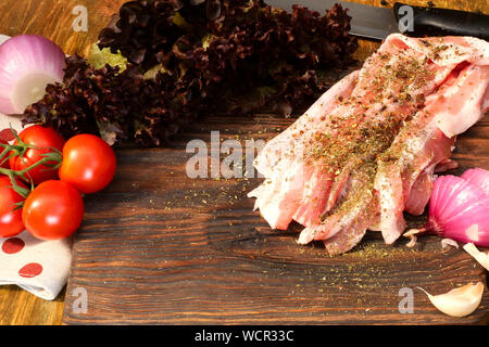 Homemade cooking. Products for delicious food. Sprinkle with spices sliced raw pork or beef brisket on wooden kitchen board, vegetables, tomatoes, let - Stock Photo