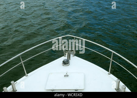 Nose of white sea ship or yacht, that cuts through the waves of the Black sea. Top view. Can be used for rippling sea, sea voyage, yachting. Close-up. - Stock Photo