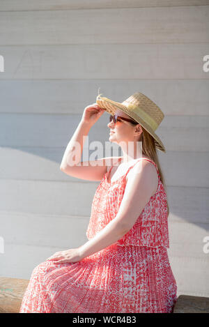Side View Of Young Woman Wearing Sun Hat While Sitting On Wooden Bench By Wall - Stock Photo