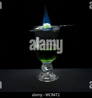 Close-up Of Alcohol In Glass On Table Against Black Background - Stock Photo