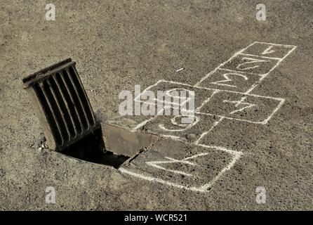 High Angle View Of Hopscotch Board Drawn By Manhole On Street - Stock Photo