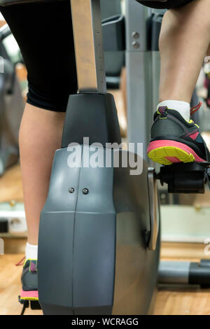 Low Section Of Woman Cycling In Gym - Stock Photo