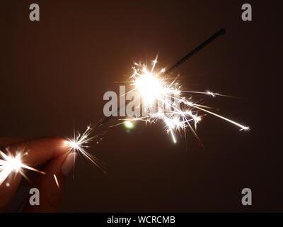 Cropped Hand Of Woman Holding Illuminated Sparkler - Stock Photo