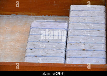 Close up blue lavender traditional beauty toilet hard soap bars in wooden box on retail display, high angle view - Stock Photo