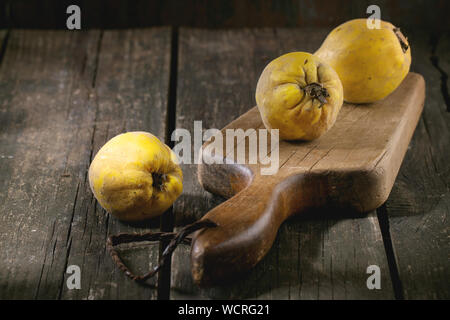 Close-up Of Fruits With Cutting Board On Wooden Table - Stock Photo