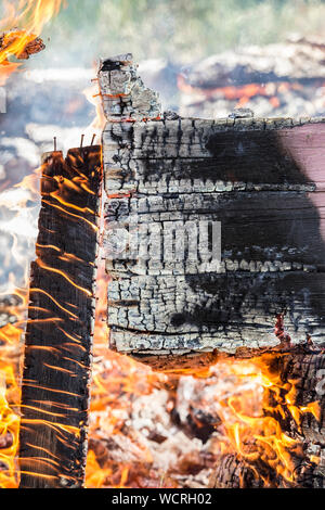 Detail view of burning painted wooden board wall fallen apart, lot of smoke, flames and charcoal. Home house fire concept. - Stock Photo