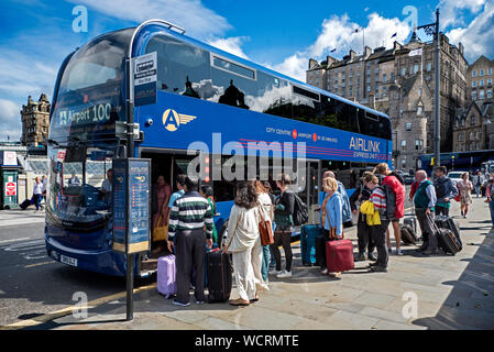 Passengers at Waverley Bridge boarding the Airlink Airport bus to take them to Edinburgh airport. - Stock Photo