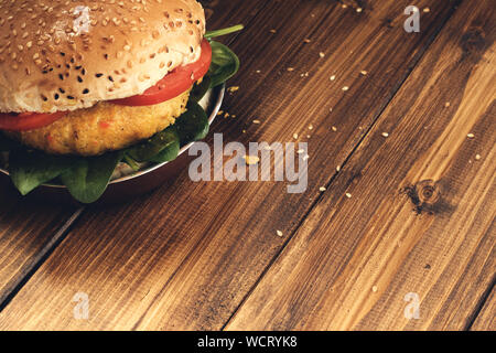 Vegetarian burger with carrot and quinoa on wooden table. - Stock Photo